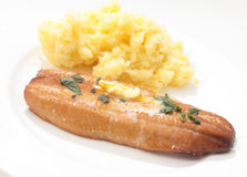 Grilled kipper and mashed potato. A grilled smoked herring or kipper, garnished with  herbs and a dab of butter, served with mashed boiled potatoes Stock Image