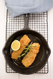 Grilled kipper with oat bran in a cast iron pan. Grilled scottish kipper with oat bran, slice lemon, rosemary in a cast iron pan Royalty Free Stock Photos