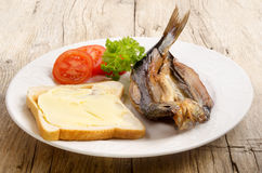 Grilled kipper on a plate. Grilled kipper with bread, tomato and parsley on a plate Stock Photos