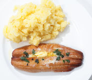 Grilled kipper and potato from above. Top view of a grilled kipper (smoked herring) garnished with butter and herbs on a plate with mashed potato Stock Photos