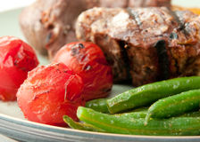 Grilled lamb chops. Seared lamb chops with grilled tomatoes and green beans Stock Photos