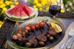 Grilled Lamb Chops In Garden. Grilled lamb chops served with cherry tomatoes, olives, and lemon. Watermelon and red wine. Outside dinner in a garden Stock Photos
