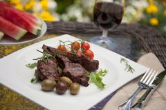 Grilled Lamb Chops. Served with cherry tomatoes and olives. Watermelon and wine. Outside dinner in a garden Royalty Free Stock Image
