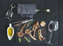 Grilled lamb chops. Rack of Lamb with garlic, rosemary, spices on slate tray, wine glass, oil in a saucer, cork screwer Royalty Free Stock Photography