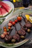 Grilled Lamb Chops In Garden. Grilled lamb chops served with cherry tomatoes, olives, and lemon. Watermelon and red wine. Outside dinner in a garden Royalty Free Stock Photo