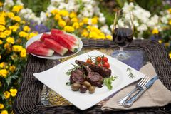 Grilled Lamb Chops. Served with cherry tomatoes and olives. Watermelon and wine. Outside dinner in a garden Stock Photos