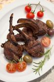 Grilled Lamb Chops. Served with cherry tomatoes and olives. Watermelon and wine. Outside dinner in a garden Royalty Free Stock Photos