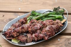 Grilled lamb kebabs with broccolini. Grilled lamb meat kebabs with green broccolini royalty free stock photos