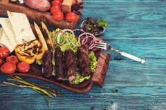 Grilled lamb meat. With vegetable on a blue wooden background Stock Images