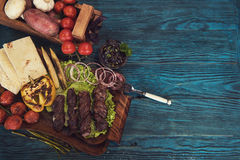 Grilled lamb meat. With vegetable on a blue wooden background Royalty Free Stock Photography