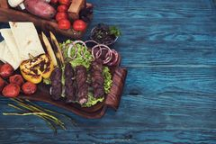 Grilled lamb meat. With vegetable on a blue wooden background Royalty Free Stock Photo