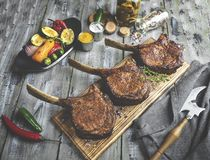 Grilled lamb,mutton meat chops with vegetables on a serving board. Rustic food concept.  stock photo