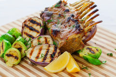 Grilled lamb rack with vegetables. On wooden board Stock Images
