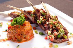 Grilled lamb ribs with herbal sauce on white ceramic tray Royalty Free Stock Photos