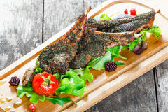 Grilled lamb ribs in herbs and greens, fresh salad, grilled vegetables and berries on cutting board on wooden background Royalty Free Stock Image