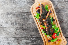 Grilled lamb ribs in herbs and greens, fresh salad, grilled vegetables and berries on cutting board on wooden background. Stock Photography