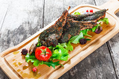 Grilled lamb ribs in herbs and greens, fresh salad, grilled vegetables and berries on cutting board on wooden background Stock Photos