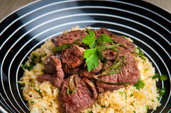 Grilled lamb on saffron rice Stock Photography