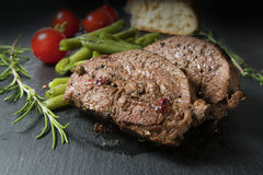 Grilled lamb steak with green beans, tomatoes and rosemary on a Royalty Free Stock Images