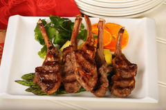 Grilled Lamp Chops. Delicious grilled lamb chops served with asparagus, mangoes and orange slices royalty free stock photo