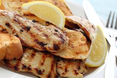 Grilled lemon chicken with garlic bread stock images