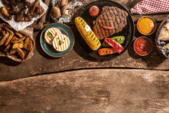 Grilled Meal Spread Out on Rustic Wooden Table stock images