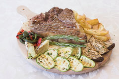 Grilled meat. Grilled italian meat with potatoes and vegetables royalty free stock photography
