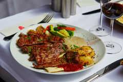Grilled meat and baked vegetables in a Turkish restaurant. Grilled meat and baked vegetables with red wine in a Turkish restaurant Stock Photo