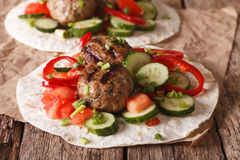 Grilled meat balls with fresh vegetables on a flat bread close u Stock Images