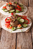 Grilled meat balls with fresh vegetables on a flat bread close u Stock Photos