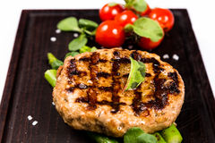Grilled meat cutlet serving with asparagus and tomatoes Stock Images
