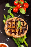 Grilled meat cutlet serving with asparagus and tomatoes Royalty Free Stock Photography