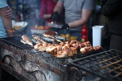 Grilled meat and fish cooked in the street food festival stock photo
