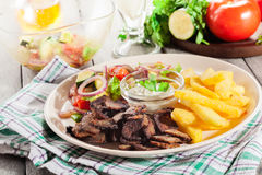 Grilled meat with French fries and fresh vegetables Royalty Free Stock Photos