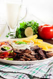 Grilled meat with French fries and fresh vegetables Stock Image