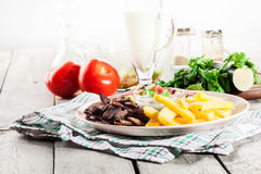 Grilled meat with French fries and fresh vegetables Royalty Free Stock Images