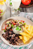 Grilled meat with French fries and fresh vegetables Stock Images