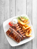 Grilled Meat, Fried Potatoes with Sauce on Plate Royalty Free Stock Image