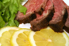 Grilled meat and lemon. Sliced grilled meat with lemon and lettuce Royalty Free Stock Photography