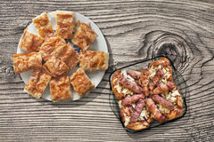 Grilled Meat Loafs Cevapcici Rolled In Bacon And Chicken Thighs In Glass Baking Pan With Gibanica Cheese Pie Set On Old Wood Stock Photos