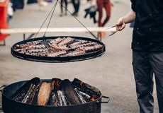 Grilled meat. man holding steel tongues and roasting beef pork o stock images