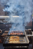 Grilled meat and meat in dough. Above the grill smoke coming from coal Stock Photography