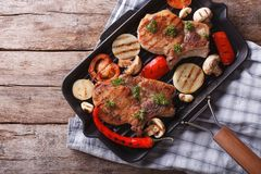 Grilled meat with mushrooms in a pan grill. horizontal top view Royalty Free Stock Photos