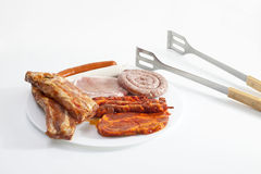 Grilled meat in plate with tongs on white background Royalty Free Stock Images