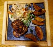grilled meat pork Παρουσιασμένος σε μια καυτή πέτρα, με τις ψημένες πατάτες και μια σαλάτα στοκ εικόνα