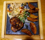 grilled meat pork 提出在一块热的石头,用被烘烤的土豆和沙拉 库存图片