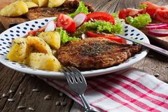 Grilled meat with salad. Grilled meat with salad and roasted potatoes Royalty Free Stock Photo