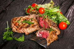 Grilled meat with salad and vegetables. Beef steak and salad on a wooden table Royalty Free Stock Photo