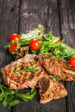 Grilled meat with salad and vegetables. Beef steak and salad on a wooden table Stock Photos