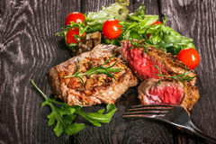Grilled meat with salad and vegetables. Beef steak and salad on a wooden table Royalty Free Stock Image